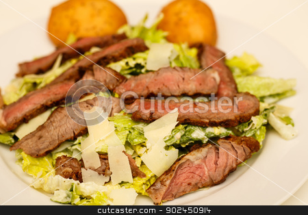 Caesar Salad with Beef Strips and Rolls stock photo, A fresh caesar salad with strips of medium-rare beef and two muffins by Darryl Brooks