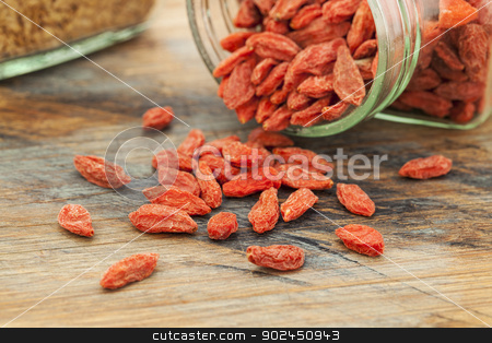 Tibetan goji berries stock photo, Tibetan goji berries (wolfberry) spilling of the glass jar on a wooden surface, selective focus by Marek Uliasz
