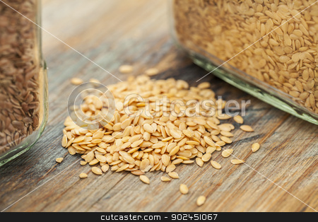 gold flax seeds stock photo, gold flax seeds on a wood background, a small pile and glass jars with a selective focus by Marek Uliasz