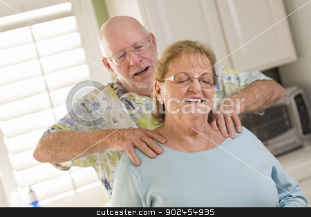Senior Adult Husband Giving Wife a Shoulder Rub stock photo, Happy Senior Adult Husband Giving Wife a Shoulder Rub in the Kitchen. by Andy Dean