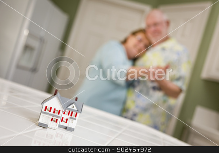 Senior Adult Couple Gazing Over Small Model Home on Counter stock photo, Happy Senior Adult Couple Dancing Together and Gazing Over Small Model Home on Their Kitchen Counter. by Andy Dean