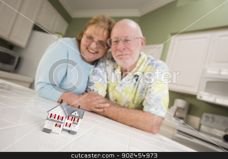 Senior Adult Couple Gazing Over Small Model Home on Counter stock photo, Happy Senior Adult Couple Gazing Over Small Model Home on Their Kitchen Counter. by Andy Dean