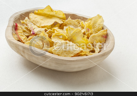 yacon tuber slices stock photo, a rustic wood bowl of dried slices of yacon tuber on white tablecloth by Marek Uliasz