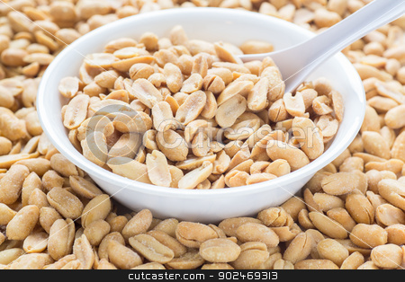 Salted Peanuts in White Bowl with Spoon stock photo, A white bowl full of and surrounded by salted and roasted peanuts with white spoon by Darryl Brooks