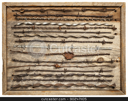 vintage barbed wire stock photo, vintage rusty barbed wire collection on isolated barn wood board by Marek Uliasz