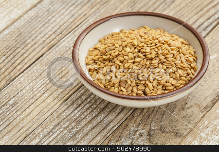 gold flax seeds stock photo, gold flax seeds in a small ceramic bowl against a grunge wood surface by Marek Uliasz