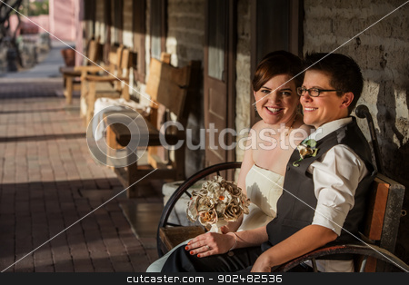 Smiling Bride with Partner stock photo, Smiling bride with partner on bench outside by Scott Griessel