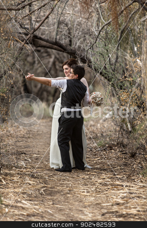 Sweethearts Dancing in Woods stock photo, Happy lesbian newlyweds dancing together in forest  by Scott Griessel