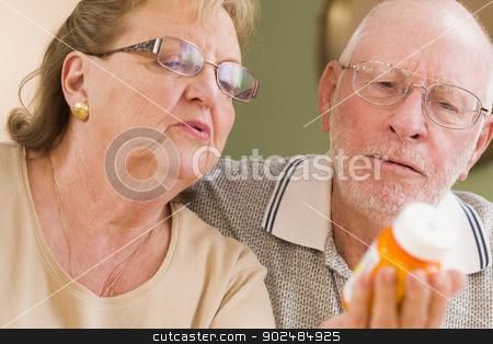 Senior Couple Reading Medicine Bottle stock photo, Curious Senior Couple Reading Prescription Medicine Bottle Together. by Andy Dean