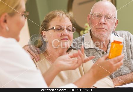 Doctor or Nurse Explaining Prescription Medicine to Senior Coupl stock photo, Doctor or Nurse Explaining Prescription Medicine to Attentive Senior Couple. by Andy Dean