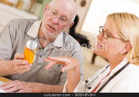 Doctor or Nurse Explaining Prescription Medicine to Senior Man stock photo, Doctor or Nurse Explaining Prescription Medicine to Attentive Senior Man. by Andy Dean