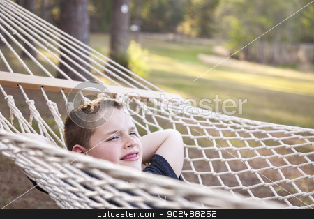Young Boy Enjoying A Day in His Hammock stock photo, Smiling Young Boy Enjoying A Day in His Hammock Outside. by Andy Dean