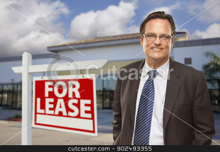 Businessman In Front of Office Building and For Lease Sign stock photo, Handsome Businessman In Front of Vacant Office Building and For Lease Real Estate Sign. by Andy Dean
