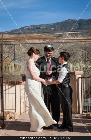 Rabbi Marrying Gay Couple stock photo, Rabbi reading sacrament for happy lesbian couple marring outdoors by Scott Griessel