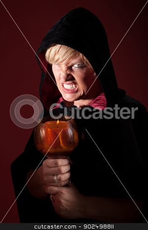 Scary Witch stock photo, Scary witch with teeth clenched and candle by Scott Griessel