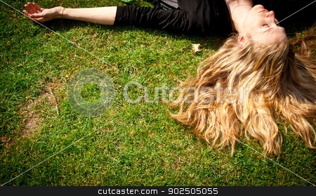 Young blonde woman lying on the grass. stock photo, Young woman with long blond hair lying on the grass sleeping or thinking. by Piccia Neri
