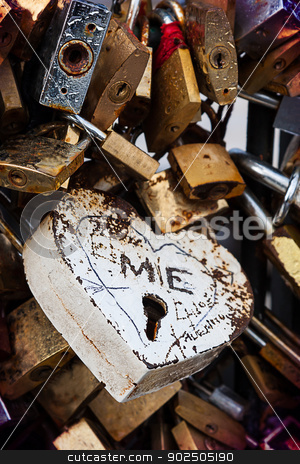 Love, locked stock photo, Detail of a love lock on the Pont de l'Archevêché, Paris, France. Lovers from all over the world lock padlocks to the bridge and toss the key in the river to signify eternal love. This custom is actually dangerous for the fragile old bridges.  by Piccia Neri
