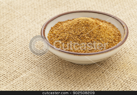 coconut palm sugar stock photo, small ceramic bowl of unrefined coconut palm sugar against a burlap canvas by Marek Uliasz