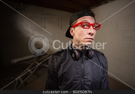 Serious Man in Red Eyeglasses stock photo, Conceited young man with red eyeglasses and earphones by Scott Griessel