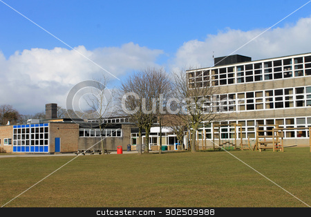Modern school building stock photo, Exterior of modern school building with playing field in foreground. by Martin Crowdy