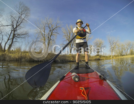 paddling stand up board stock photo, mature male paddler on a red stand up paddleboard (SUP), calm lake in Colorado, early spring by Marek Uliasz