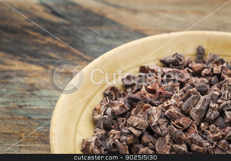 raw cacao nibs stock photo, Raw cacao nibs in a small ceramic bowl against grunge wooden background by Marek Uliasz