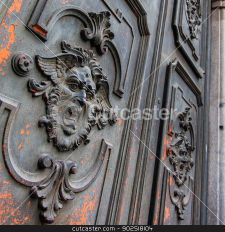 Mysterious door stock photo, Gothic mask on an old wodden door in Milan - Italy by Paolo Gallo