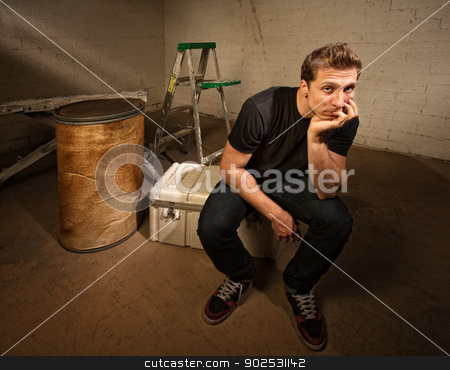 Bored Laborer Sitting stock photo, Bored laborer sitting on cooler in unfinished basement by Scott Griessel