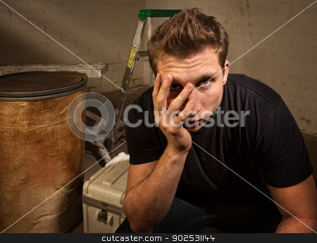 Unhappy Man Sitting stock photo, Unhappy young white man sitting on crate indoors by Scott Griessel