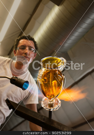 Glass Artisan Working stock photo, Handsome latino glass artisan finishing a yellow vase by Scott Griessel