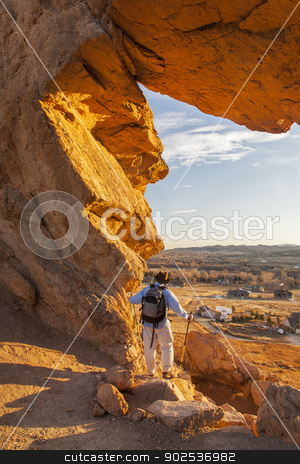 hiker at Devils Backbone stock photo, male hiker looking through a keyhole in Devil's Backbone Open Space at foothills of Rocky Mountains near Loveland, Colorado, warm sunset light by Marek Uliasz