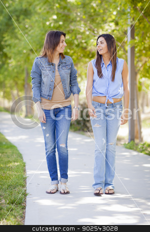 Young Adult Mixed Race Twin Sisters Walking Together stock photo, Young Adult Mixed Race Twin Sisters Walking Together Outside. by Andy Dean