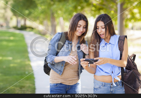 Young Adult Mixed Race Twin Sisters Sharing Cell Phone Experienc stock photo, Young Adult Mixed Race Twin Sisters Sharing Cell Phone Experience Outside. by Andy Dean