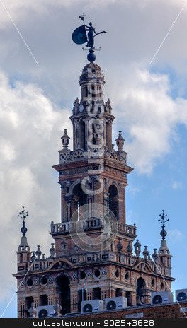 Bell Tower Cathedral of Saint Mary of the See Spire Weather Vane stock photo, Spire, Bell Tower, Seville Cathedral, Cathedral of Saint Mary of the See, Seville, Andalusia Spain.  Built in the 1500s.  Largest Gothic Cathedral in the World and Third Largest Church in the World.  Burial Place of Christopher Columbus. by William Perry