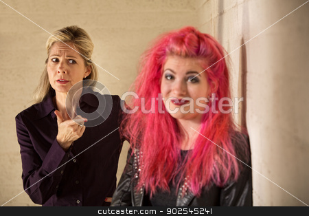 Smiling Woman and Mother stock photo, Concerned mother pointing at grinning daughter in pink hair by Scott Griessel