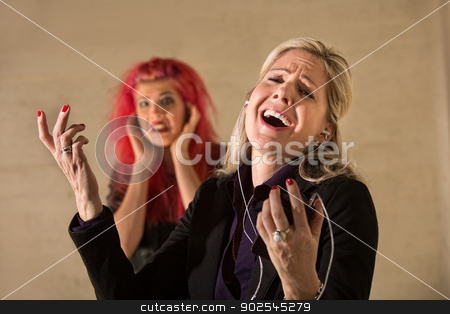 Happy Woman Singling Aloud stock photo, Happy woman singing loudly with annoyed teenager nearby by Scott Griessel