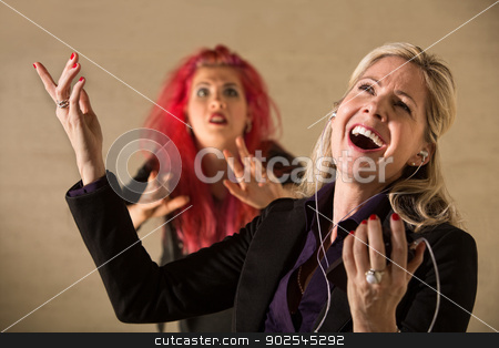 Rude Woman Singing stock photo, Embarrassed teen in pink hair with singing parent holding mp3 device by Scott Griessel