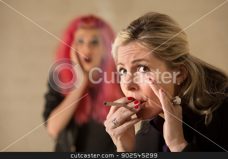 Woman Sneaking a Cigarette stock photo, Surprised teen behind mature woman smoking a cigarette by Scott Griessel