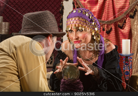 Beautiful Soothsayer Makes Prediction stock photo, Grinning European fortune teller with hands over crystal ball by Scott Griessel