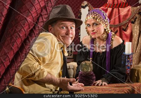 Fortune Teller and Skeptical Man stock photo, Fortune teller in head scarf with skeptical customer and crystal ball by Scott Griessel