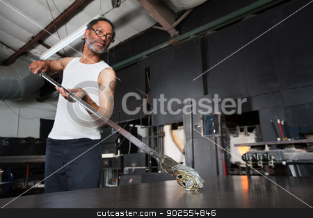 Glass Artist with Piece on Workbench stock photo, Mature glass artisan turning rod with small vase by Scott Griessel
