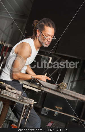 Glass Art Worker stock photo, Busy African man working with fine art glass object in factory by Scott Griessel