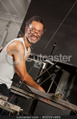 Smiling Glass Art Worker stock photo, Confident Black glass artisan working on metal workbench by Scott Griessel