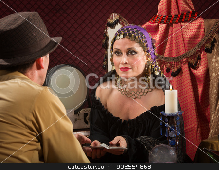 Woman with Tarot Cards stock photo, Calm beautiful tarot card reader with male client by Scott Griessel