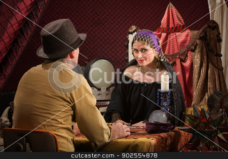 Customer with Fortune Teller stock photo, Smiling beautiful fortune teller with crystal ball and customer by Scott Griessel