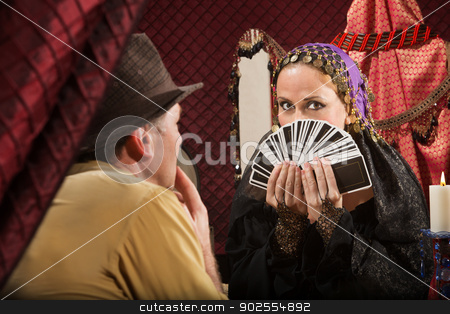 Customer Chooses a Tarot Card stock photo, Attractive gypsy fortune partially covered by tarot cards by Scott Griessel