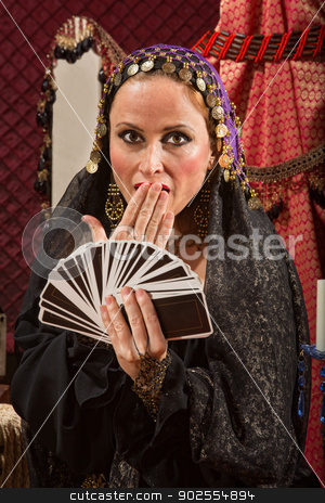 Surprised Female Fortune Teller stock photo, Surprised gypsy fortune teller with hand of tarot cards by Scott Griessel