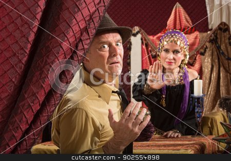 Man Sees Gypsy's Evil Eye stock photo, Cursed man and female fortune teller with crystal ball by Scott Griessel