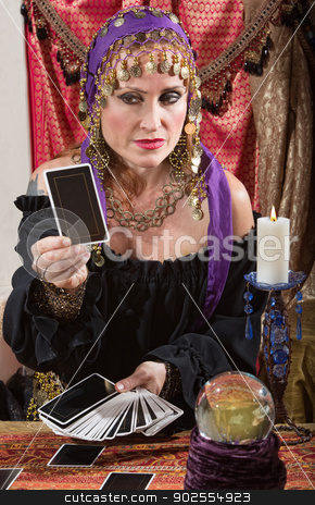 Stoic Fortune Teller stock photo, Stoic Roma lady looking at a tarot card indoors by Scott Griessel