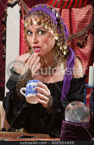 Surprised Reading Tea Leaves stock photo, Surprised fortune teller reading tea leaves cup by Scott Griessel